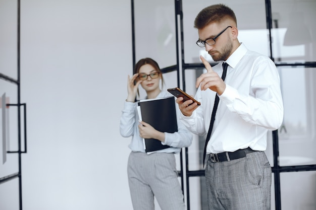 여자는 폴더를 보유하고있다. 비즈니스 회의에서 비즈니스 파트너입니다. 남자는 전화를 사용합니다. 안경을 가진 사람