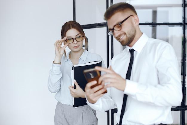 女性はフォルダを持っています。ビジネスミーティングでのビジネスパートナー。男性は電話を使用します。眼鏡をかけている人