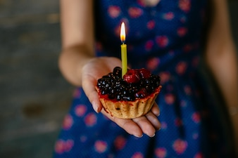 Woman holds a fruit cupcake with candle. Close-up view.