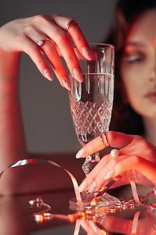 女性は彼女の美しさの手にガラスガラスを持っています。テーブルの上の指輪とジュエリー、贅沢な生活。アルコール依存症