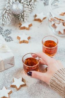 女性はウイスキー、ブランデー、または酒のグラスを持っています。白い背景の上のクッキー、飲み物、冬の休日の装飾。季節の休日のコンセプト。