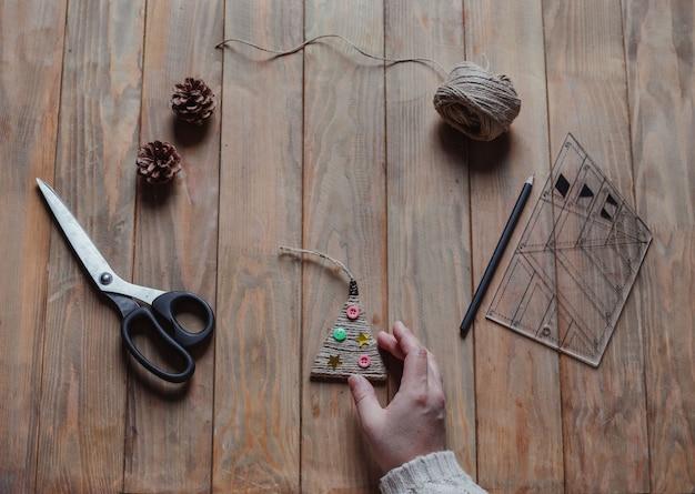 女性は手に手作りのクリスマスツリーのおもちゃを持っています