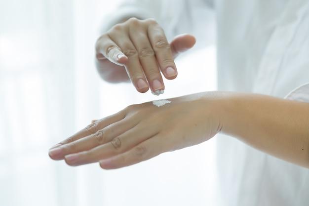여자는 그녀의 손에 화장품 크림 항아리를 보유
