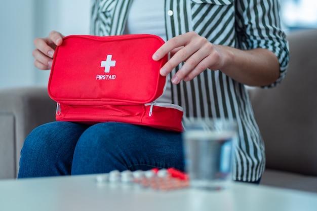 Женщина держит аптечку с лекарством у себя дома. первая помощь при боли и болезни