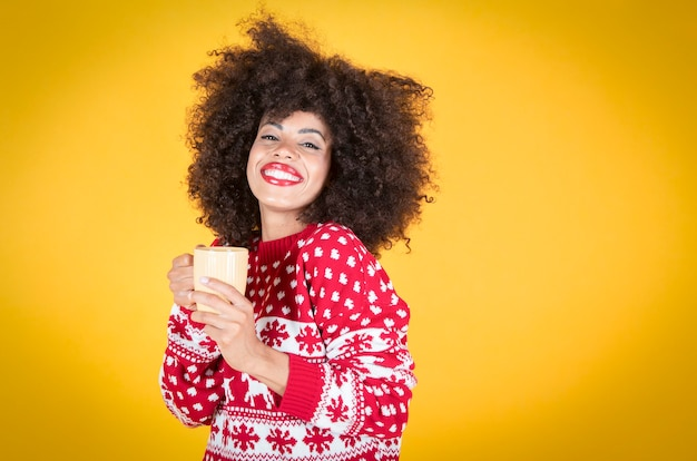 女性はクリスマスにマグカップ、黄色の背景を保持します