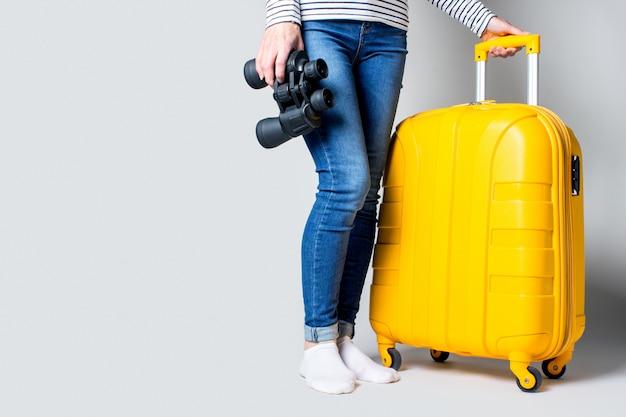 Женщина держит пластиковый желтый чемодан и бинокль на светлом пространстве. концепция путешествия, ожидание рейса, отпуск. видны только ноги.