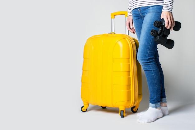 Женщина держит пластиковый желтый чемодан и бинокль на светлом месте. концепция путешествия, ожидание полета, отпуск.