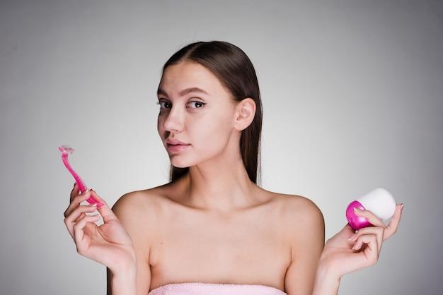 Женщина держит в руках бритву и дезодорант
