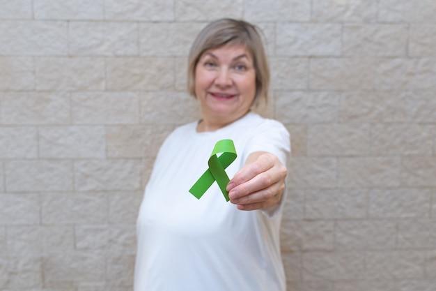 Женщина держит табличку с зеленой лентой для информирования и поддержки людей, живущих с болезнями.