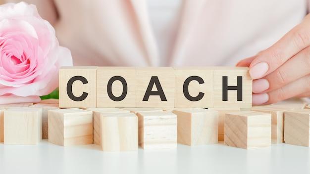 女性は、コーチのテキストを手にした木製の立方体を持っています。木製の立方体には生きたバラの花があります。ピンクの背景、正面図。ビジネス、経済、教育の概念