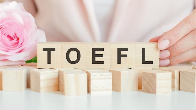 女性は、toeflのテキストを手にした木製の立方体を持っています。木製の立方体には生きたバラの花があります。ピンクの背景、正面図。ビジネス、経済、教育の概念