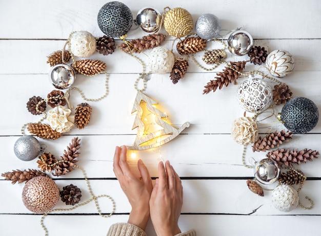 女性は白い木製の壁にクローズアップの光るライトで木のおもちゃを持っています。