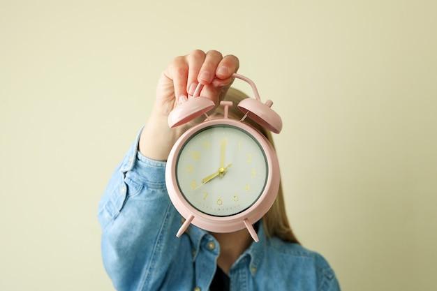 Женщина держит будильник на бежевой поверхности
