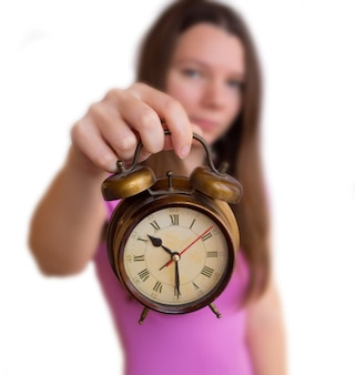 Woman holds an alarm clock on a white background. time change to winter or summer time