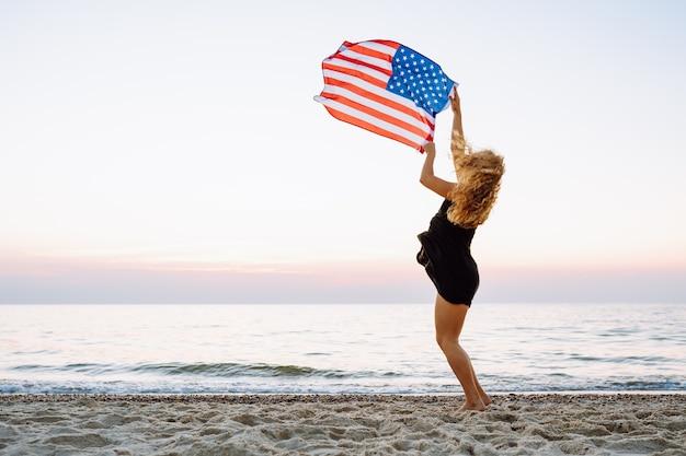 Женщина держит американский флаг и прыгает на пляже.