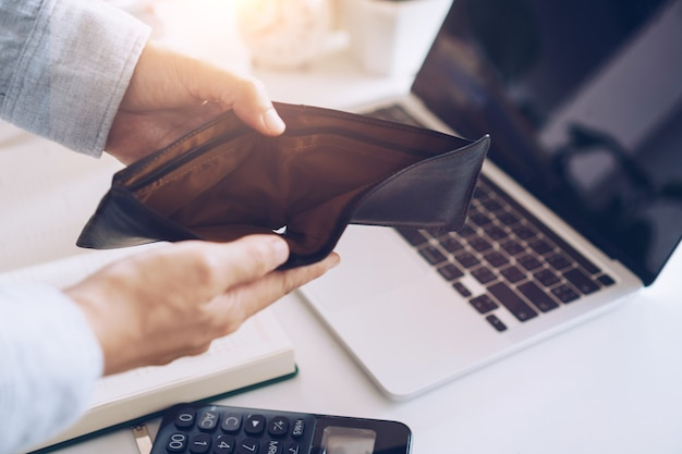 Женщина держит пустой кошелек и монеты в руке, что означает денежную финансовую проблему или банкротство без работы, разорение после получения зарплаты по кредитной карте, концепцию долга.