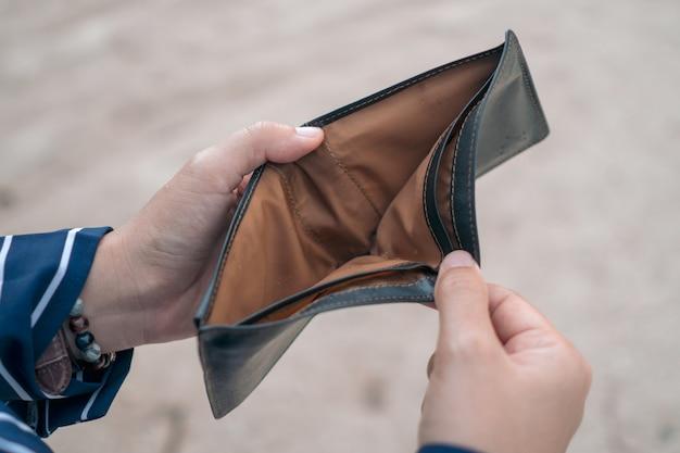 Женщина держит пустой кошелек и монеты в руке, что означает финансовые проблемы с деньгами или банкротство безработных, сломанных после выплаты зарплаты по кредитной карте.