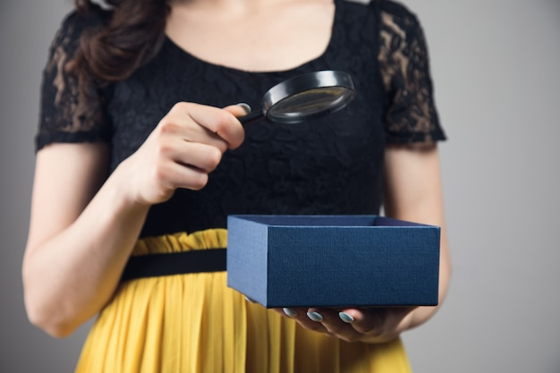 여자는 열린 상자를 들고 돋보기를 통해 봅니다.