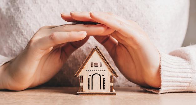 女性は薄ピンク色の表面に太陽を当てて手で木造住宅を保持し、保護します。甘い家