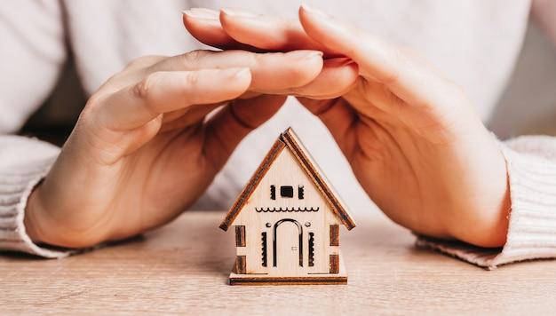 女性は手や保険で木造住宅を手に持って守っています。甘い家