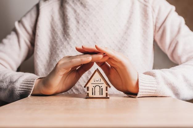 女性は明るいピンクの背景に太陽と彼女の手で木造住宅を保持し、保護します。甘い家