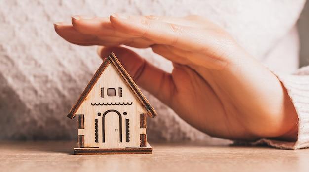 Женщина держит и защищает деревянный дом руками с солнцем на светло-розовом фоне. милый дом