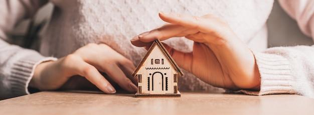 여자는 밝은 분홍색 배경에 태양과 함께 그녀의 손으로 목조 주택을 보유하고 보호합니다. 편하고 달콤한 집