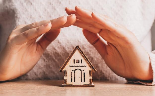 여자는 밝은 분홍색 공간에 태양과 함께 그녀의 손으로 목조 주택을 보유하고 보호합니다.