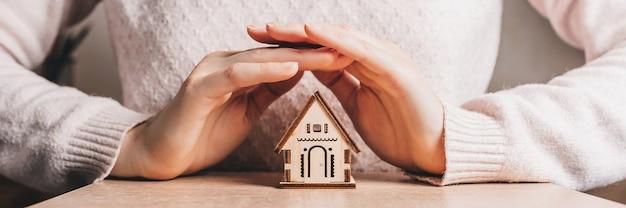 女性はピンク色の表面に太陽を当てて手で木造住宅を保持し、保護します。甘い家