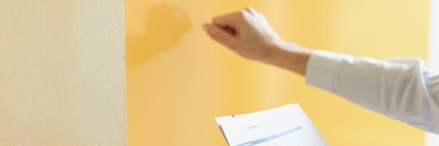 Женщина держит форму заявки в руке и стучит в дверь