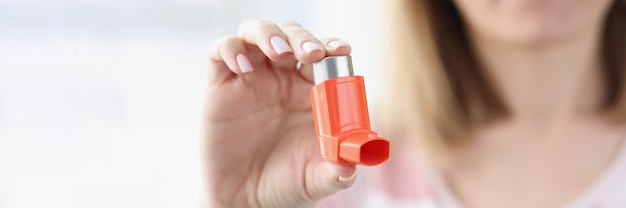Woman holds an asthma inhaler in her hand treatment of bronchial asthma concept
