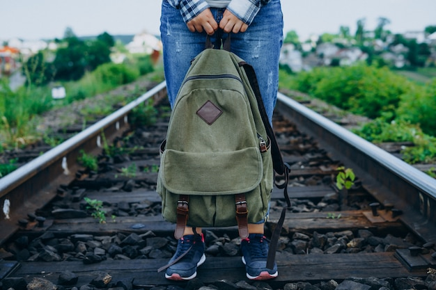 Woman holds backpack and stands on railway track.