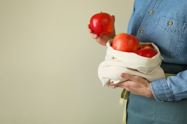 여자는 잘 익은 빨간 사과와 가방을 보유