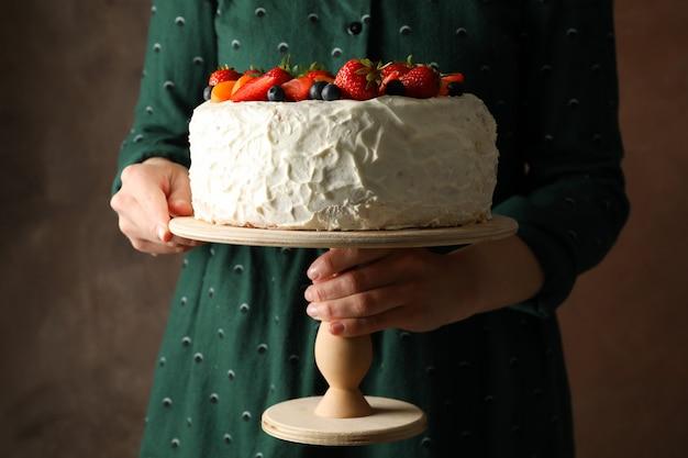 女性は茶色の背景にベリークリームケーキを保持しています。美味しいデザート