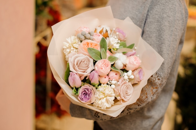 Woman holds a big bouquet with roses, pion-shaped roses and eucalyptus
