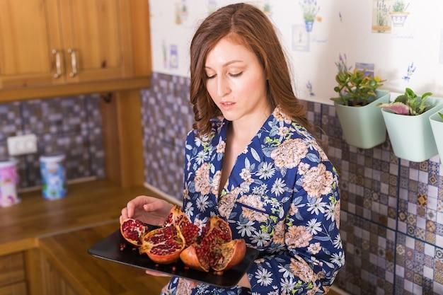 Женщина держит большой спелый красный гранат