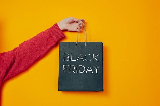 Woman holds black bag. black friday image on the orange background. hand and black friday bag.