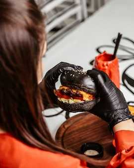 女性は手で黒チーズバーガーを保持します