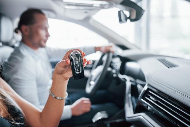 Женщина держит ключи черного цвета. позитивный менеджер показывает покупательнице особенности новой машины.