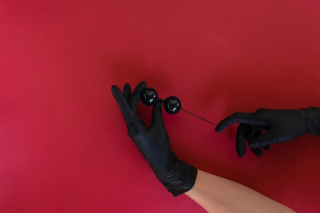 A woman holds black vaginal balls ready for muscles exercises. strong vaginal muscles
