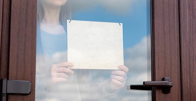 Женщина держит пустой деревянный знак за стеклянной дверью
