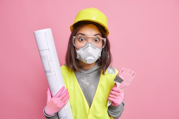 Woman holds blueprint and painting brush wears protective helmet glasses and uniform works on building and repairing