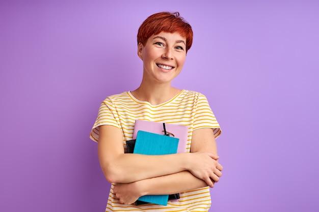 Женщина держит книги в руках и позирует, изолированные на фиолетовой стене. молодая рыжая женщина любит учиться, образование