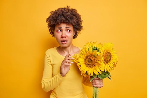해바라기 꽃다발을 들고 있는 여성은 빨간 눈을 가지고 있으며 선명한 노란색 위에 격리된 캐주얼 점퍼를 착용합니다