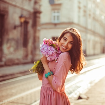Woman holds bouquet tightly posing on morning street