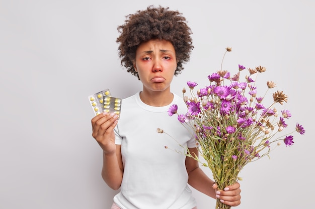 Woman holds bouquet of wildflowers and pills on allergy has red watery eyes looks with sad expression isolated over white