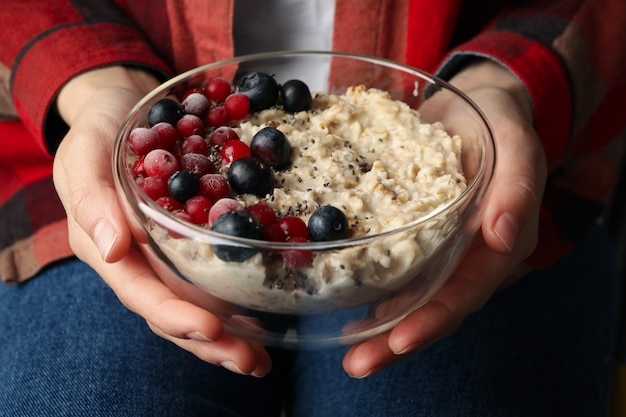 Woman holds bowl with oatmeal porridge with fruits. close up