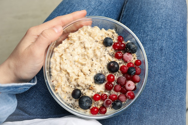 Woman holds bowl with oatmeal porridge with fruits, top view