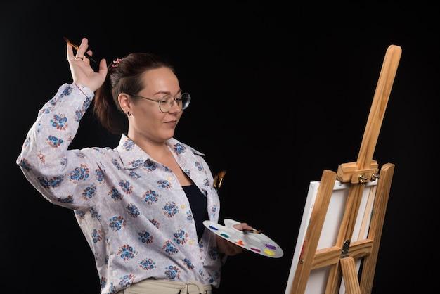 Женщина держит кисть и краски на черном фоне