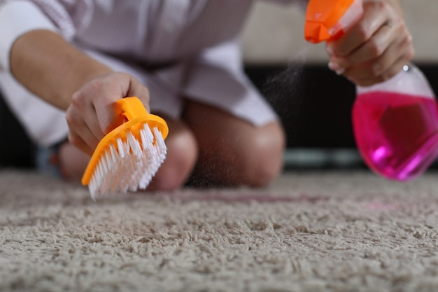 Woman holds brush and cleaning spray on carpet